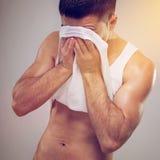Молодой человек утомленной пригонки обтирая пот с его стороны Стоковые Фотографии RF