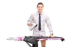Молодой человек утюжа его брюки стоковая фотография
