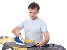 Молодой человек утюжа его серые изолированные брюки стоковые фото