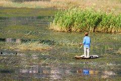 Молодой человек удя самостоятельно на бамбуковой шлюпке Стоковое Фото