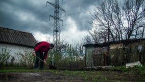 Молодой человек фермера выкапывает землю с старым пакостным лопаткоулавливателем в саде Промежуток времени сток-видео