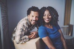 Молодой человек чёрного африканца и его коробки подруги moving в новый дом совместно и делающ красивую жизнь жизнерадостно Стоковое фото RF