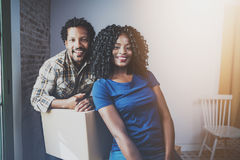 Молодой человек чёрного африканца и его коробки подруги moving в новый дом совместно и делающ красивую жизнь жизнерадостно Стоковые Изображения RF
