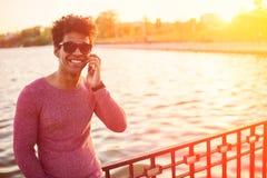 Молодой человек чёрного африканца с сотовым телефоном над солнечным светом Стоковое Изображение RF