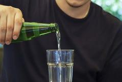 Молодой человек льет минеральную воду Стоковая Фотография RF