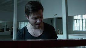 Молодой человек эмоционально поет на рояле Сексуальный человек в футболке с большим взрезом и с цепью вокруг его видеоматериал