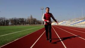 Молодой человек Active подходящий красивый идя делающ низкий протягивать нагревать muscles внешняя разминка стадиона в замедленно акции видеоматериалы