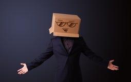 Молодой человек gesturing с картонной коробкой на его головке с smiley Стоковые Изображения RF
