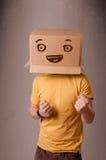 Молодой человек gesturing с картонной коробкой на его головке с smiley Стоковое фото RF