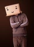 Молодой человек gesturing с картонной коробкой на его головке с smiley Стоковая Фотография RF