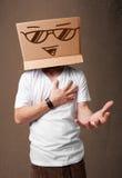 Молодой человек gesturing с картонной коробкой на его головке с smiley Стоковое Фото