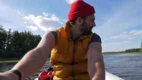 Молодой человек Hipser кавказца смешанной гонки гребя раздувную шлюпку с деревянными веслами на озере Отснятый видеоматериал обра акции видеоматериалы