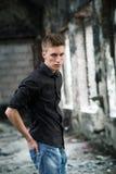 Молодой человек yog портрета в рубашке и джинсах стоя на покинутой предпосылке Стоковое фото RF