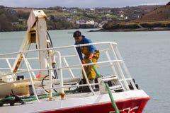 Молодой член команды на смычке траулера как она стыкует в гавани Kinsale в пробочке графства на южном береге Ирландии Стоковое фото RF