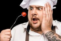 Молодой шеф-повар держа томат вишни на вилке изолированной на черноте Стоковые Фотографии RF