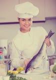 Молодой шеф-повар держа тушу радужной форели Стоковое фото RF