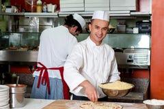 Молодой шеф-повар делая пиццу на кухне стоковая фотография rf