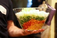 Молодой шеф-повар подготавливая овощи на плите в кухне ресторана Стоковое Изображение RF