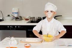 Молодой шеф-повар с мукой на его стороне стоковое изображение