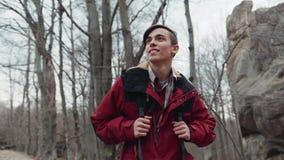 Молодой backpacker идя через дезертированный лес, счастливо усмехающся и наблюдающ пейзажем Упаденный сезон осени, сток-видео