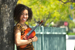Молодой biracial скрипач усмехаясь и полагаясь против дерева стоковое изображение rf