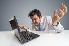 Молодой confused и неуверенный человек работает с компьтер-книжкой стоковая фотография