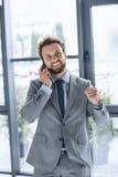 Молодой excited бизнесмен говоря на smartphone в офисе Стоковое Изображение