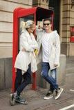 Молодой gossiping пар на телефоне Стоковая Фотография