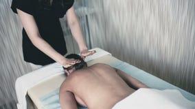 Молодой masseuse кладет масло на ` s девушки назад видеоматериал