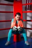 Молодой sporty женский боксер с полотенцем вокруг ее усаживания i шеи стоковое изображение rf