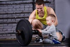 Молодой sporty отец показывая гантели для его маленького сына и усмехаясь против кирпичной стены в спортзале креста подходящем Стоковые Фотографии RF