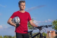 Молодой Sporty человек велосипедиста держа его велосипед Outdoors Стоковое Изображение