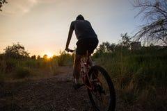 Молодой sporty человек ехать велосипед на заходе солнца Стоковые Изображения