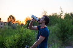 Молодой sporty человек ехать питьевая вода велосипеда от бутылки спорта на заходе солнца Стоковые Изображения