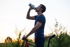 Молодой sporty человек ехать питьевая вода велосипеда от бутылки спорта на заходе солнца Стоковое Фото
