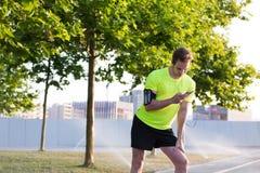 Молодой sporty человек прочитал текстовое сообщение на его умном телефоне пока принимающ пролом во время jog утра в красивом горо стоковая фотография rf