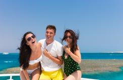 Молодость смеясь над и стоя на яхте на солнечном летнем дне Стоковые Изображения