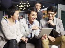 Молодые азиатские бизнесмены используя таблетку в офисе Стоковое Фото