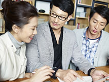 Молодые азиатские бизнесмены работая совместно в офисе Стоковая Фотография