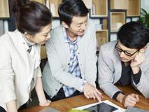 Молодые азиатские бизнесмены работая совместно в офисе Стоковое фото RF
