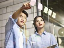 Молодые азиатские бизнесмены работая совместно в офисе Стоковые Изображения