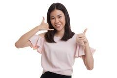 Молодые азиатские большие пальцы руки женщины вверх показывают с жестом телефона Стоковые Изображения