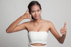 Молодые азиатские большие пальцы руки женщины вверх показывают с жестом телефона Стоковое Изображение