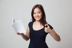 Молодые азиатские большие пальцы руки женщины вверх с книгой Стоковое Изображение RF