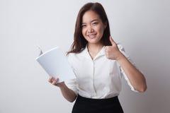 Молодые азиатские большие пальцы руки женщины вверх с книгой Стоковое Изображение