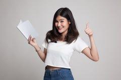 Молодые азиатские большие пальцы руки женщины вверх с книгой Стоковые Изображения RF