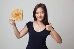 Молодые азиатские большие пальцы руки женщины вверх с подарочной коробкой Стоковые Изображения RF