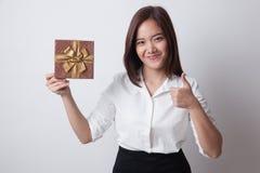 Молодые азиатские большие пальцы руки женщины вверх с подарочной коробкой Стоковая Фотография
