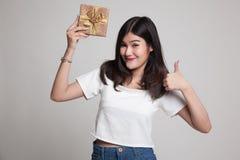 Молодые азиатские большие пальцы руки женщины вверх с подарочной коробкой Стоковые Изображения