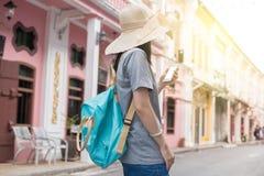 Молодые азиатские блоггер или backpacker путешествовать используя применение трассы на мобильном телефоне найти необходимый адрес Стоковые Фото